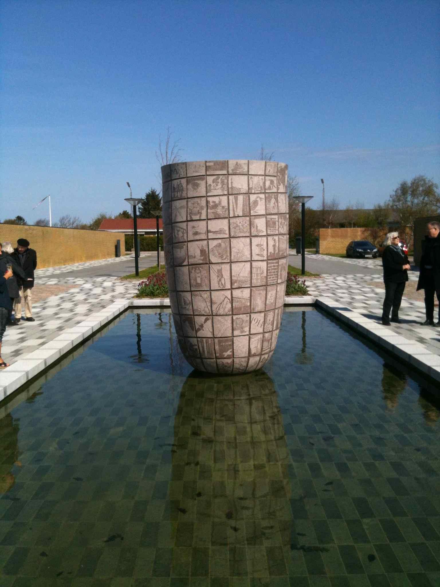 Bemærk hvordan skulpturen både spejles og fordobler bassinbundens mønster. Fra indvielsen af Laila Westergaards 'Granat' på Hjørring Kaserne, april 2014